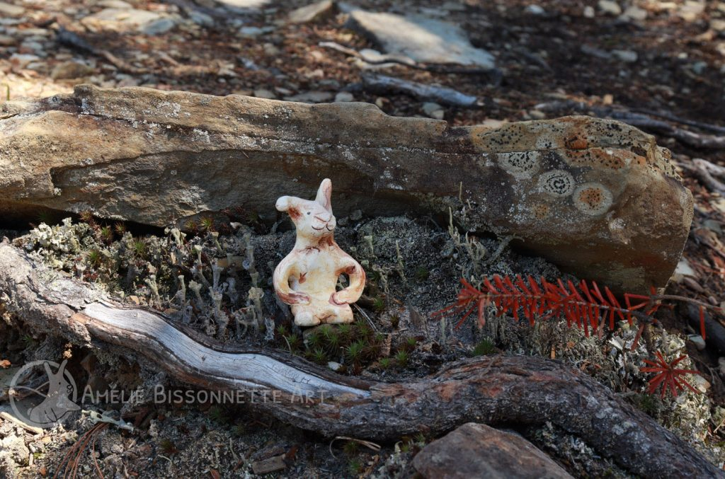 knealing bunny in a mossy recess under a protruding rock