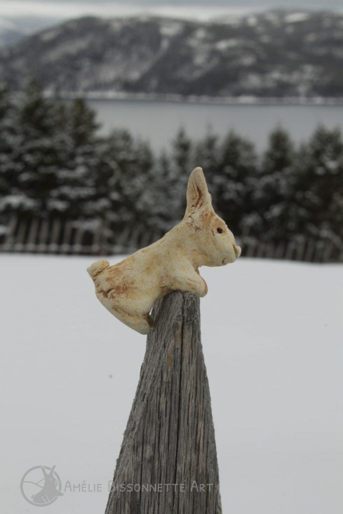 Du haut d'un pieu de clôture pointu, un petit lapin contemple les montagnes enneigées environnantes