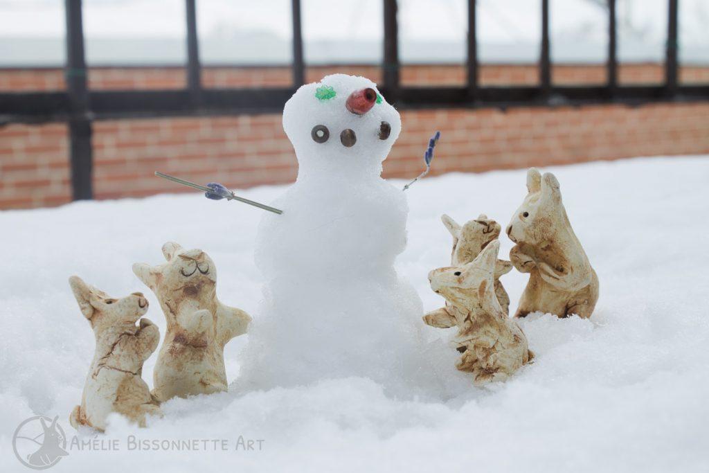 des lapins regardent le bonhomme de neige qu'ils ont fait