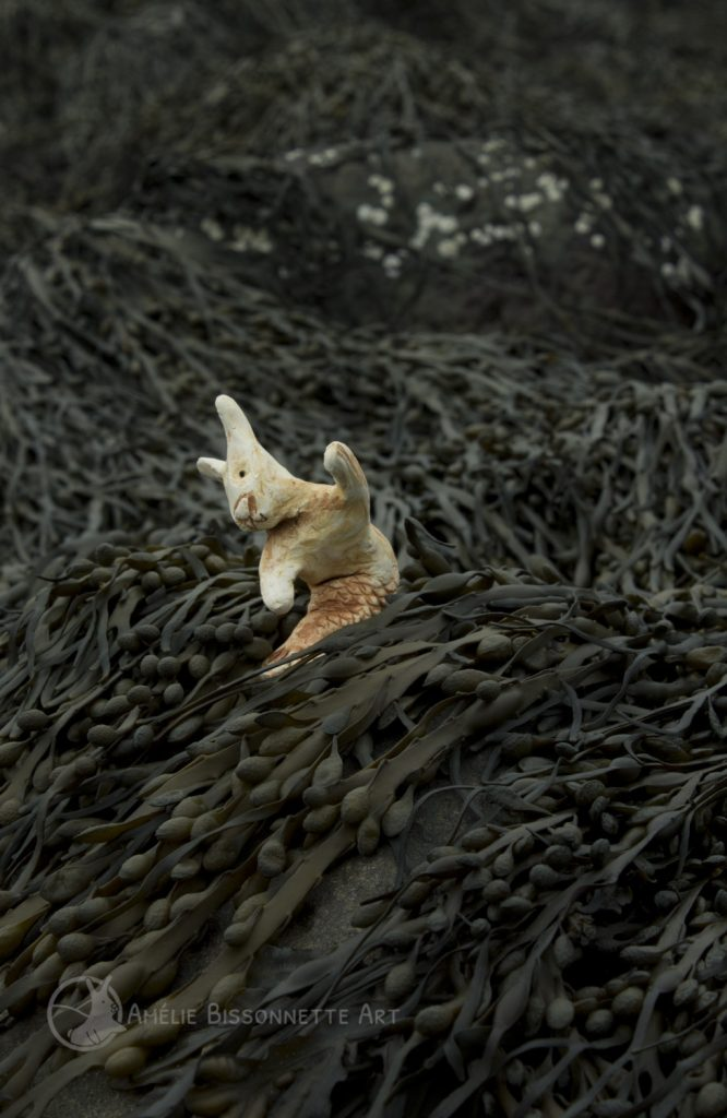 One small mermaid bunny about to dive sideways into the seaweeds