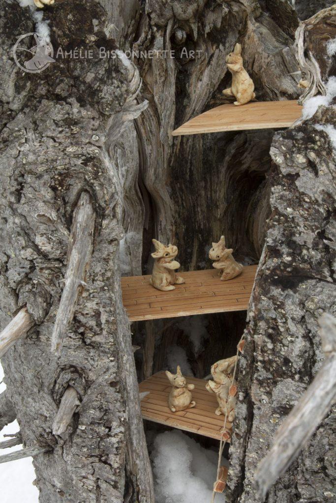 petits lapins vivant sur trois plateformes-planchers dans un tronc d'arbre. Les trois niveaux sont atteignables via une échelle de corde