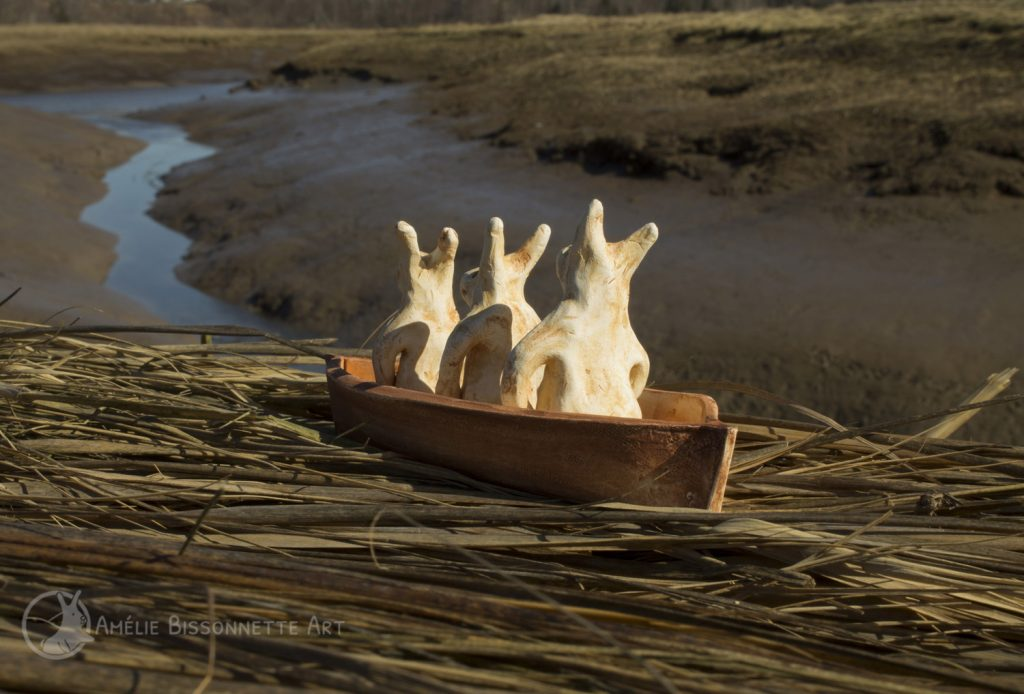 Three tiny bunnies stalled in a boat next to a clay creek