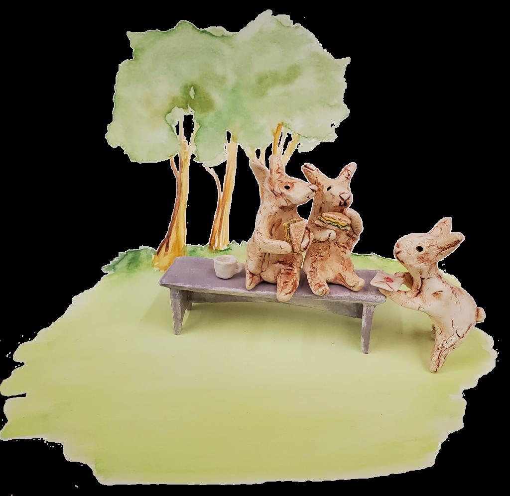Illustration de deux lapins mangeant des sandwichs pendant qu'un troisième apporte une lettre. Ils sont assis sur un banc avec des arbres derrière