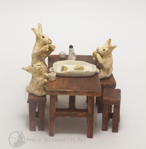 Trois lapins mangent des sandwichs, assis sur des tabourets hauts autour d'une table de bois
