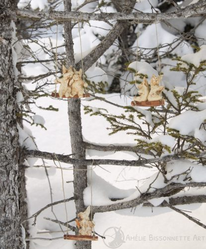 Cinq lapins sur trois balançoires accrochées à de fines branches. Deux couples occupent les deux balancelles du haut, tandis qu'un autre lapin, assis plus bas, mange une carotte.
