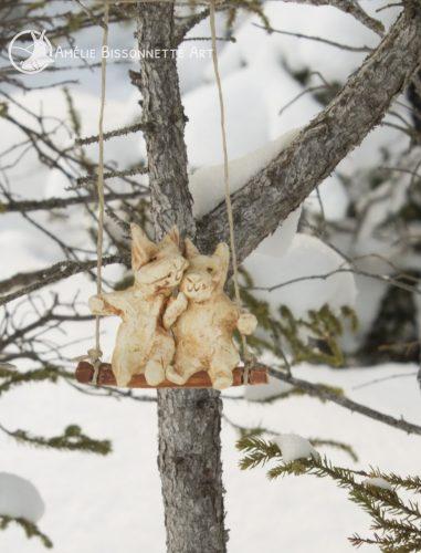 Deux petits lapins amoureux se pelotonnent sur une balançoire avec la neige et les branches en arrière-plan