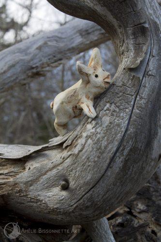 un lapin poucet, perché sur une branche sèche et recourbée