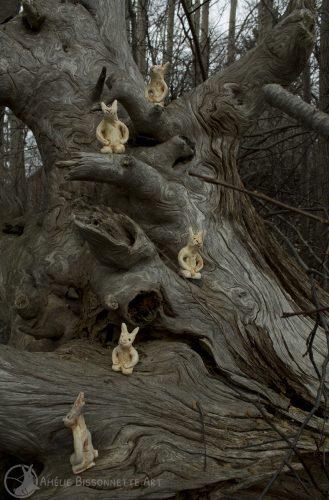 cinq figurines de lapins montant la garde sur une souche sèche, positionnés à différentes hauteurs