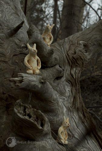 3 petits lapins perchés sur des branches sèches
