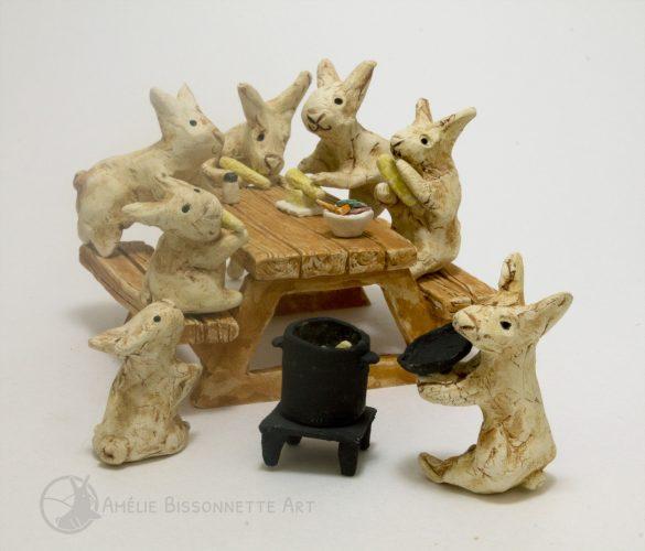 fête de lapins autour d'une table de pique-nique. Ils mangent des épis de maïs cuits dans un gros chaudron noir