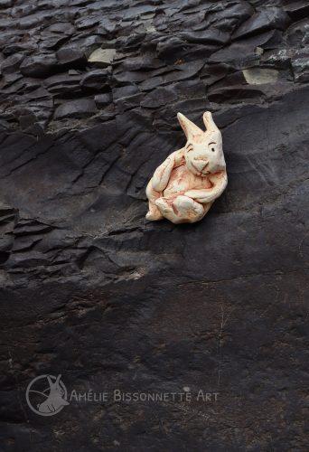 lapin couché sur roche texturée sombre. Il fait un clin d'œil.