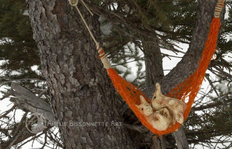 2 lapins anthropomorphes se câlinent dans un hamac orange vif