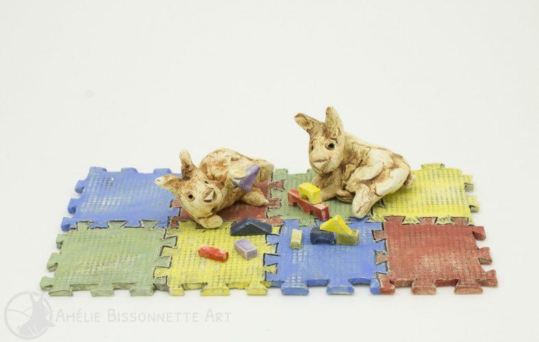 deux lapins jouent avec des blocs sur des tuiles colorées de plancher en mousse