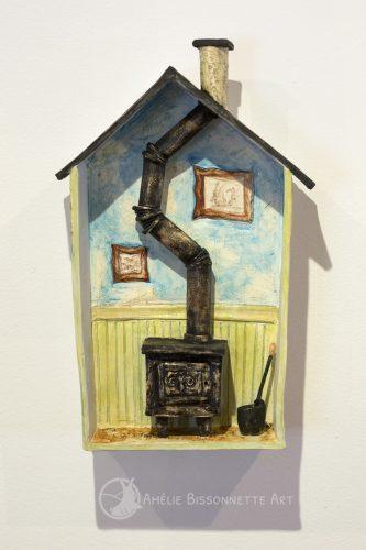 sculpture d'un petit chalet avec un poêle à bois en fonte et un tuyau de cheminée sinueux. La moitié inférieure des murs est en lattes de bois vertes et le haut est bleu, décoré avec deux dessins encadrés.