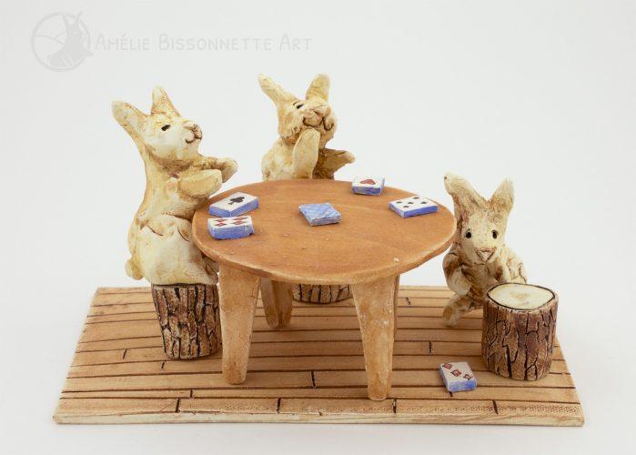 trois lapins souriants jouent aux cartes autour d'une table. L'un ramasse des cartes échappées sur le plancher de bois. Les deux autres le regardent et sont assis sur des tabourets faits avec des buches.