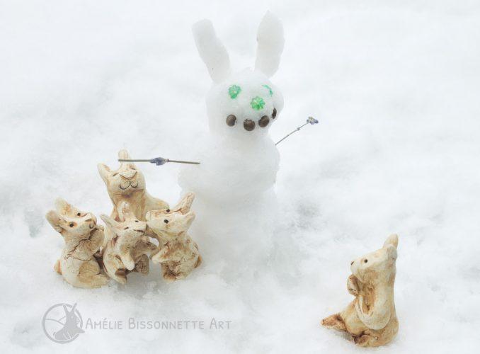un groupe de lapins autour d'une sculpture de neige de bonhomme-lapin