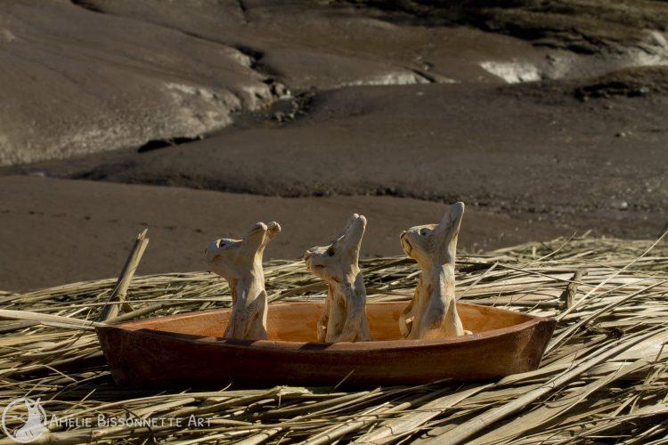 vue de côté de 3 minuscules lapins assis dans un bateau non loin de grandes collines d'argile mouillée