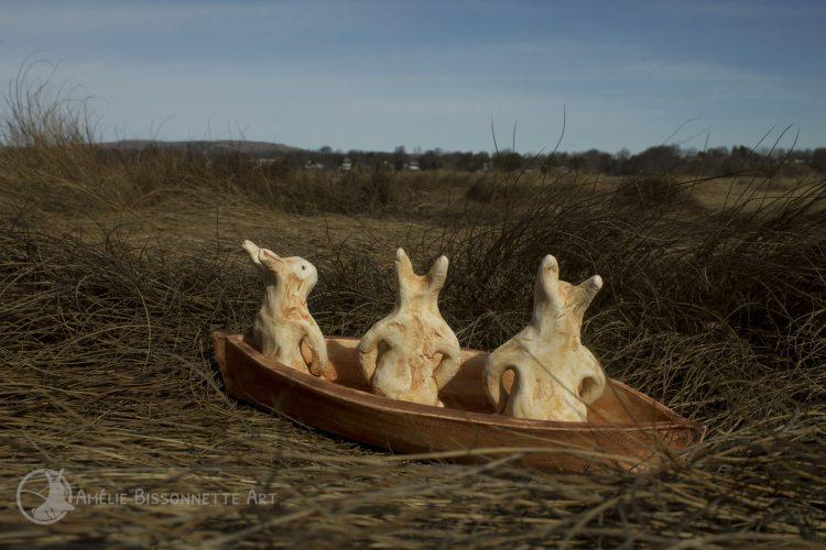 3 petits lapins dans un bateau parmi les herbes sèches lors d'une journée venteuse
