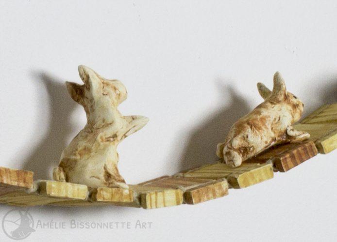 deux lapins traversent un pont suspendu aux côtés d'un cadre de bois